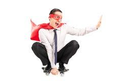 Überglücklicher männlicher Superheld, der ein kleines Skateboard reitet Lizenzfreie Stockbilder
