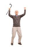 Überglücklicher Senior, der einen Stock oben schauen hält Stockfoto