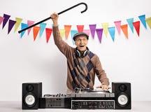Überglücklicher Senior mit einem Stock, der Musik auf einer Drehscheibe spielt Stockfotografie