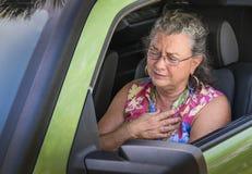 Überhitzter frustrierter älterer Frauenfahrer mit plötzlichem Schmerz in der Brust Lizenzfreie Stockbilder