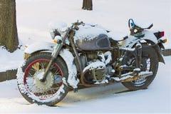 Überholtes Modell des alten Motorrades auf einem schneebedeckten Parkplatz am Morgen Lizenzfreies Stockbild