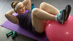 Überladene Dame, die Presse-oben tut, trainiert mit gymnastischem Ball zu Hause, Training stockfotografie
