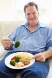 Überladene Fleisch fressende gesunde Mahlzeit, die auf Sofa sitzt Stockbild