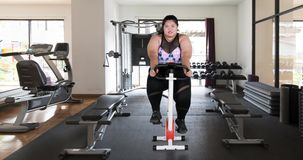 Überladene Frau in der Sportkleidung, die in Turnhalle radfährt stock footage