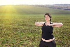 Überladene Frau, die Übungen in der Landschaft tut Stockbild