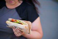 Überladene Frau, die das Sandwich draußen geht isst lizenzfreies stockbild