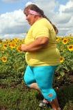 Überladene Frau, die entlang Feld von Sonnenblumen läuft Lizenzfreie Stockbilder