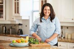 Überladene Frau, die Gemüse in der Küche vorbereitet stockfotografie