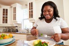 Überladene Frau, die gesunde Mahlzeit in der Küche isst Lizenzfreies Stockfoto