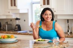 Überladene Frau, die gesunde Mahlzeit in der Küche isst Stockfoto