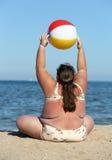 Überladene Frau, die Gymnastik auf Strand tut Stockfotografie