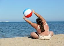 Überladene Frau, die Gymnastik auf Strand tut Stockfotos