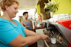 Überladene Frau, die Kaffee in der Turnhalle macht Stockbild