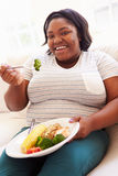 Überladene Frau, welche die gesunde Mahlzeit sitzt auf Sofa isst Lizenzfreies Stockbild