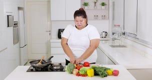 Überladene junge Frau, die Gemüse vorbereitet stock footage