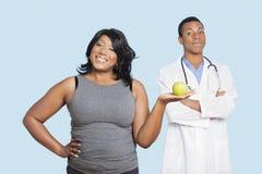 Überladene Mischrassefrau, die grünen Apfel mit Doktor über blauem Hintergrund hält Lizenzfreie Stockfotos