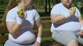 Überladene Paare, die saftige Äpfel nach Training, gesunden Imbiss, nährend essen stock video footage