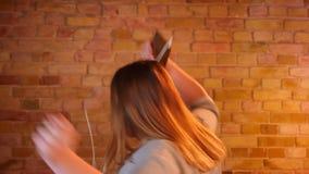 Überladene Studentin hört Musik in den Kopfhörern aktiv und, die froh in gemütliche Hauptatmosphäre tanzen stock video
