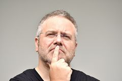 Überladener erwachsener Mann, der eine Entscheidungs-tragende Gläser macht lizenzfreies stockbild