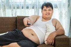 Überladener Kerl, der auf der Couch sitzt, um irgendein fernzusehen Lizenzfreies Stockfoto
