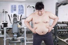 Überladener Kerl hält seinen Magen an der Turnhalle Stockfoto