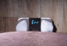 Überladener Mann betrachtet ein Fehlerzeichen einer Gewichtungsskala Stockfotografie
