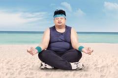 Überladener Mann, der Yoga auf Strand tut Stockfoto