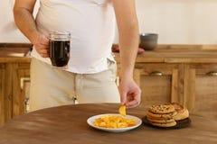 Überladener Mann mit ungesunder ungesunder Fertigkost und Bier stockfoto