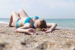Überladenes blondes Ein Sonnenbad nehmen auf Kieselküste Lizenzfreies Stockfoto