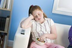 Überladenes Mädchen, das auf Sofa schläft Lizenzfreie Stockbilder