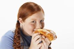 Überladenes Mädchen, das Gebäck isst lizenzfreies stockfoto