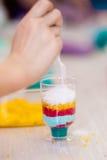 Überlagerung des farbigen Salzes im Glas stockbild