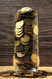 Überlastungsmünzen im Glas lizenzfreie stockbilder