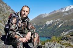 Überleben im wilden Ein Mann in der Tarnung, die unter den Bergen stillsteht Jäger, überleben im Wald lizenzfreies stockfoto