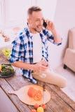 Übermütiger Mann, der ein Gespräch mit einem Freund am Telefon hat lizenzfreie stockbilder