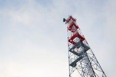 Übermittler und Antennen auf Telekommunikation ragen, Sonnenuntergang im schneebedeckten Land hoch stockbilder