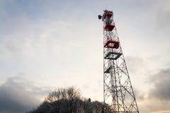 Übermittler und Antennen auf Telekommunikation ragen, Sonnenuntergang im schneebedeckten Land hoch stockfotografie