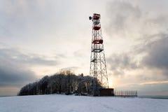 Übermittler und Antennen auf Telekommunikation ragen, Sonnenuntergang im schneebedeckten Land hoch lizenzfreie stockfotografie