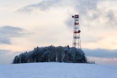 Übermittler und Antennen auf Telekommunikation ragen, Sonnenuntergang im schneebedeckten Land hoch stockfoto