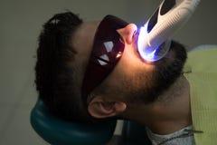 Überprüfen Sie vom jungen Mann durch Zahnarzt auf hellem unscharfem Hintergrund Schönes europäisches Mannlächeln mit gesunder Zah stockfoto