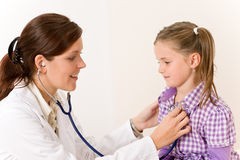 Überprüfenkind des weiblichen Doktors mit Stethoskop stockbild