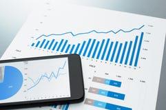 Überprüfung des Finanzberichts Dokument und intelligentes Telefon Lizenzfreie Stockbilder