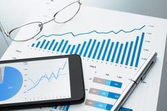 Überprüfung des Finanzberichts Dokument und Smartphone Lizenzfreie Stockbilder