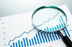 Überprüfung des Finanzberichts Wachstumstabelle mit betrachtend, vergrößern Sie Stockfotografie