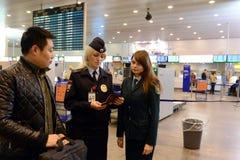 Überprüfung von Dokumenten von den fremden Passagieren am Flughafen Sheremetyevo Lizenzfreies Stockbild