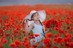 Überraschen nah herauf Porträt des reizenden netten jungen romantischen Mädchens mit der Mohnblumenblume in der Hand, die auf Fel stockfotografie