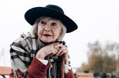 Überraschende ältere Frau, die auf ihren besten Freund wartet stockfoto