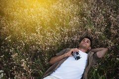 Überraschende Ansicht von oben des hübschen jungen Mannes mit Weinlesekamera, liegend auf Wiesenhintergrund Reisestimmung Entspan lizenzfreie stockfotos