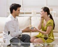 Überraschende Frau des Mannes mit elegantem Geschenk Stockbild