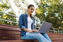 Überraschende junge Schönheit, die draußen unter Verwendung der Laptop-Computers sitzt stockbilder